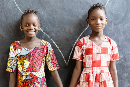 Gorgeous African Sisters Posing, Smiling and Laughing Happy in Front of Blackboard at School
