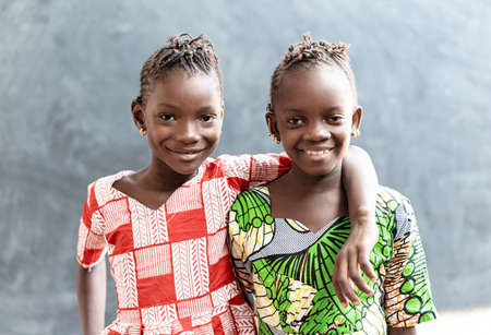 Two African Sisters Laughing and Smiling Outdoors with Toothy Smiles before School Archivio Fotografico