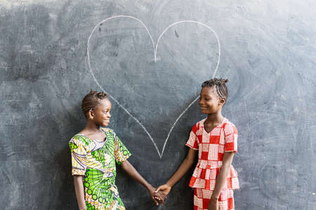 Two Cute African Girls Women Standing Together with Heart Love Symbol in Blackboard Background Archivio Fotografico