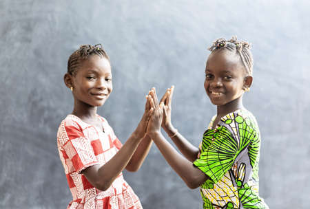 Candid Photo of Two African Children Sisters Girls Women Playing Cheerful Smile with Hands and Faces