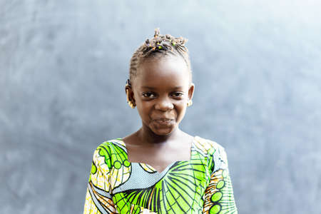 Cute African Beautiful Child Smiling Happy in front of Blackboard in Typical African Classroom