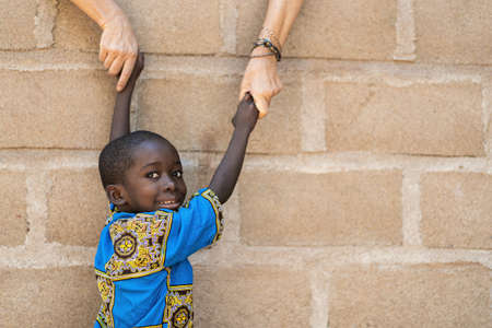 Smiling African Black Boy Gets Help from White Caucasian Woman in front of Wall