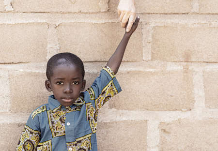 Little African Black Boy Holding Hands with White Caucasian Volunteer Coming to Africa to Help