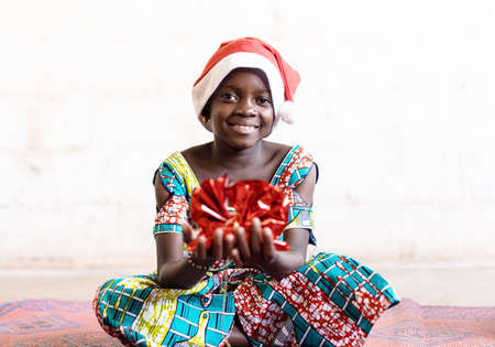 Cute Christmas African Black Girl with Funny Hat and Red Present at Home in Bamako, Mali