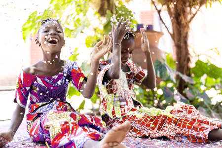 Beautiful young black African women celebrating new year and chrismas party while blowing confetti decorations to camera