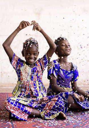 Portrait View of African ethnic group of children enjoying party indoors with confetti