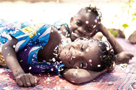 Birthday Party and Holiday Concept by Celebrating happiness, young African girls with big smiles and confetti