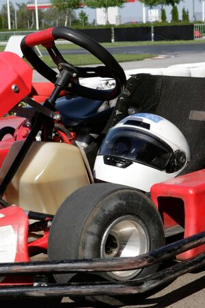 helmet seat: Go Cart in the pit stop closeup with a helmet in the seat and race track in the background. Stock Photo
