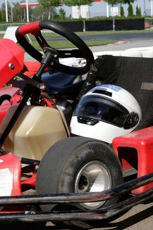 pit stop: Ir de compra en el primer plano parada en boxes con un casco en el asiento y la pista de carreras en el fondo.