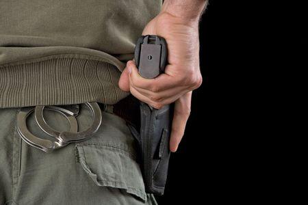 holster: Oficial de la polic�a militar sobre la celebraci�n de la mano una pistola en una funda. Foto de archivo
