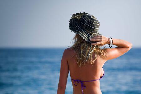 Bikini girl with a hat watching the horizon over water. photo
