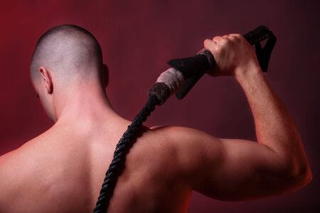 and the horizontal man: Close-up of a muscular male preparing to strike with his whip. Rear view.   Stock Photo