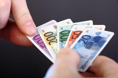 fake money: Man choosing Five Hundred Euro Banknote, but plastic, fake money, toy. Stock Photo
