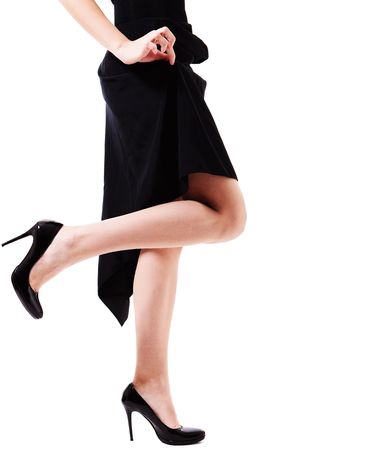 Waist-down view of woman's legs in black high heels. She is standing on one leg against white background, while pinching her black dress up. Stock Photo - 6193078