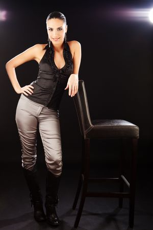 Brunette fashion girl standing beside the bar chair and looking at camera. photo