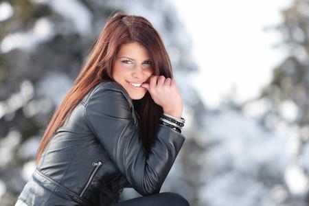 chaqueta de cuero: Mujer joven sonriendo a la cámara con el dedo en la boca.