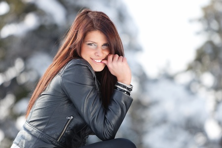leather jacket: Young woman smiling into the camera with finger in her mouth.