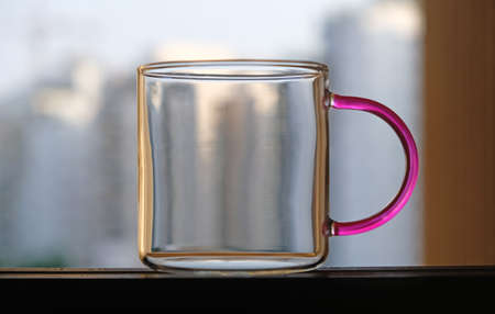 A glass mug with a colored handle, standing in the window aperture.