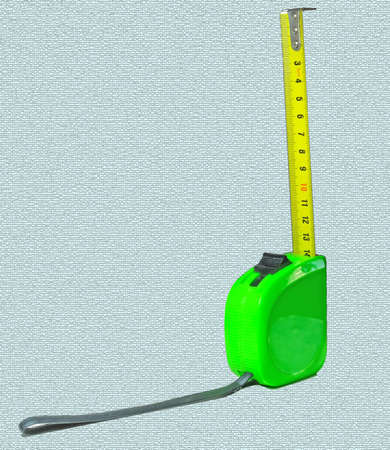 Measuring tape in green plastic case with yellow metal measuring tape. Stockfoto