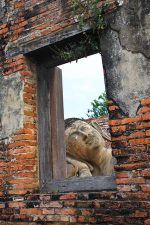 buddha into window on old brick wall,Thailand photo