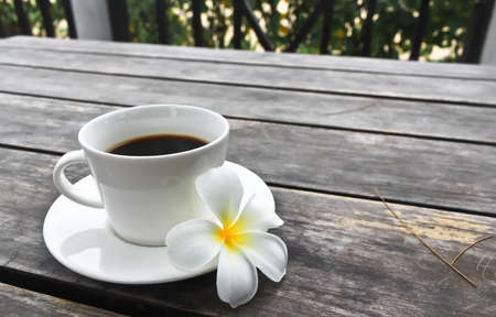 Coffee cup and Frangipani Flower on the wooden table photo