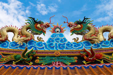 colorful dragon statue on china temple roof with blue sky background photo