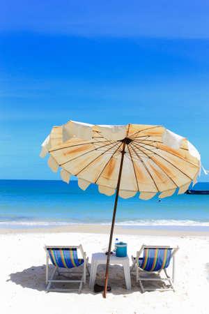 Beach chair and umbrella on idyllic tropical sand beach in holidays.