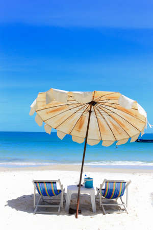 Beach chair and umbrella on idyllic tropical sand beach in holidays. photo