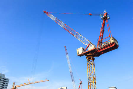 cranes at the construction site against blue sky Stock Photo