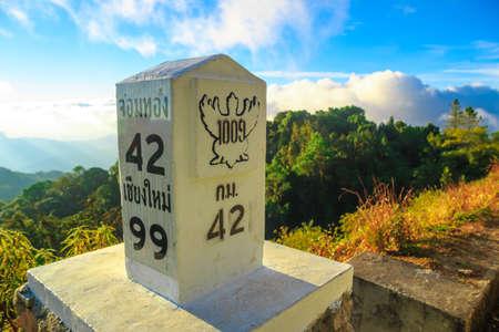 milestone: Milestone at the roadside with mountain landscape Stock Photo