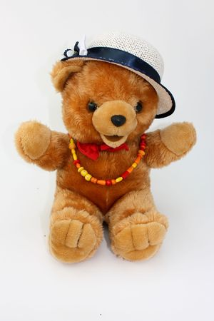 playthings: Beautiful teddy-bear with red tie, hat and a necklace Stock Photo