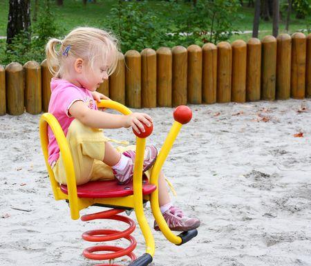 Little girl having fun ridding a spring swing