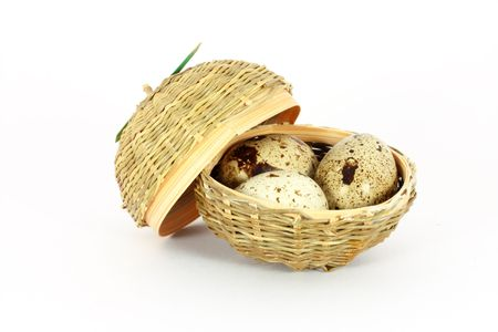 japanese quail: Three eggs of japanese quail in a little basket isolated on white