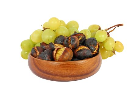 Roasted chestnuts in a wooden bowl and grape isolated on white photo
