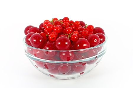 Sweet cherry and red currants in glass bowl isolated on white photo