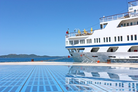 mirrored: Stern of cruise ship mirrored in glass plates of Monument to the Sun in Zadar harbor Croatia