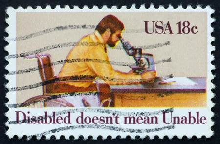 UNITED STATES OF AMERICA - CIRCA 1981: a stamp printed in the United States of America shows Disabled Man Looking through Microscope, circa 1981 photo