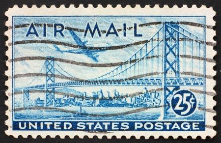UNITED STATES OF AMERICA - CIRCA 1947: a stamp printed in the United States of America shows plane over San Francisco � Oakland Bay Bridge, circa 1947 스톡 콘텐츠