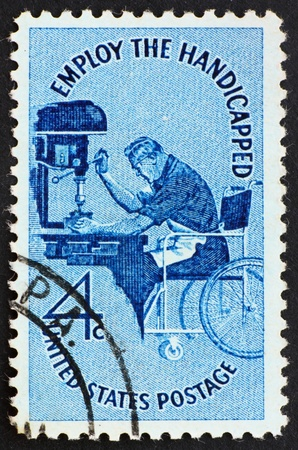 UNITED STATES OF AMERICA - CIRCA 1960: a stamp printed in the United States of America shows Man in wheelchair operating drill press, Employ the Handicapped, circa 1960 photo