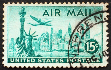 UNITED STATES OF AMERICA - CIRCA 1947: a stamp printed in the United States of America shows plane over Statue of Liberty and New York Skyline, circa 1947 Imagens - 10750840