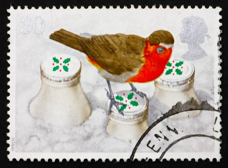 GREAT BRITAIN - CIRCA 1995: a stamp printed in the Great Britain shows European Robin on snow covered milk bottle, circa 1995 photo