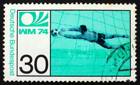 GERMANY - CIRCA 1974: a stamp printed in the Germany shows Soccer Goalkeeper and Emblem, World Cup Soccer Championship, Munich, circa 1974 photo