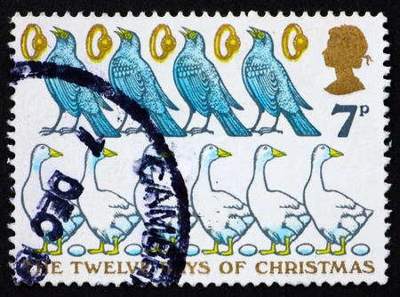 GREAT BRITAIN - CIRCA 1977: a stamp printed in the Great Britain shows Four Colly Birds, Five Gold Rings, six Geese a-laying, the Twelve Days of Christmas, circa 1977 photo