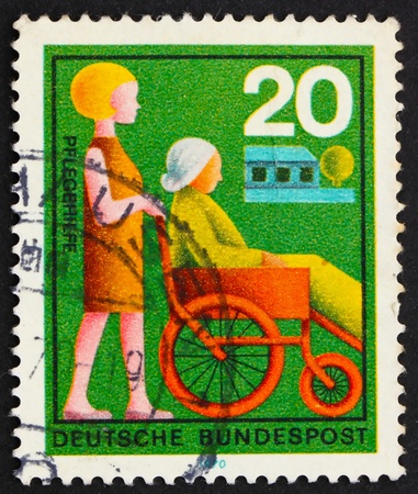 GERMANY - CIRCA 1970: a stamp printed in the Germany shows Nurse Assisting Elderly Woman, circa 1970 photo