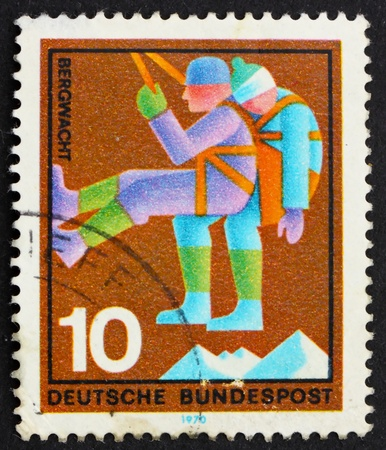 GERMANY - CIRCA 1970: a stamp printed in the Germany shows Mountain Climber, rescuer bringing down casualty, honoring various voluntary services, circa 1970 photo