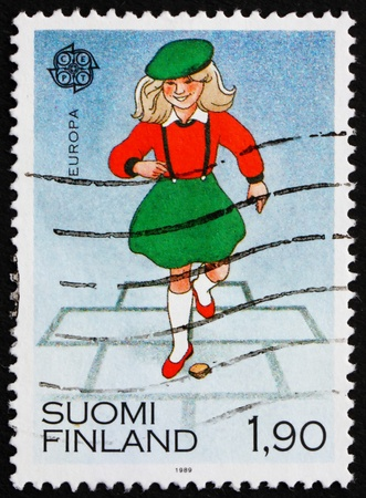 FINLAND - CIRCA 1989: a stamp printed in the Finland shows Little Girl at Play, Hopscotch, circa 1989 photo