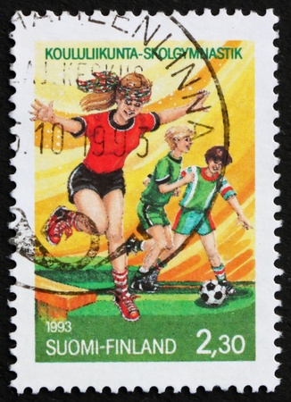 educacion fisica: FINLANDIA - CIRCA 1993: un sello impreso en Finlandia muestra ni�os jugando, 150 aniversario de la Educaci�n F�sica en las escuelas finlandesas, alrededor del a�o 1993 Foto de archivo