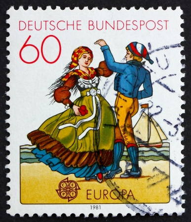 GERMANY - CIRCA 1981: a stamp printed in the Germany shows North German couple dancing in regional costumes, circa 1981 스톡 콘텐츠