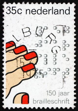 NETHERLANDS - CIRCA 1975: a stamp printed in the Netherlands shows Fingers Reading Braille, Sesquicentennial of the Invention of Braille system of writing for the Blind, circa 1975 Stock Photo - 12179568