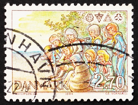 DENMARK - CIRCA 1984: a stamp printed in the Denmark shows Scouts around Campfire and Emblems, circa 1984 photo